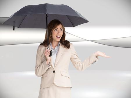Composite image of elegant businesswoman holding black umbrella against white background photo