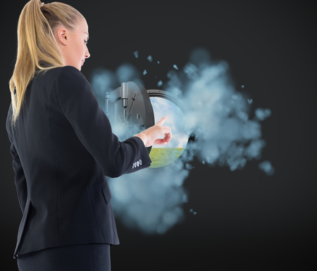Composite image of blonde businesswoman pointing somewhere photo