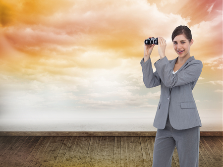 Composite image of businesswoman posing with binoculars photo