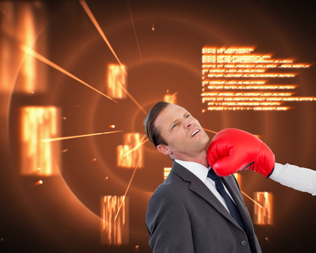 Composite image of businesswoman hitting colleague with her boxing gloves on white background photo
