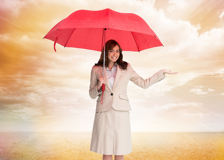 Composite image of happy brunette businesswoman holding umbrella photo