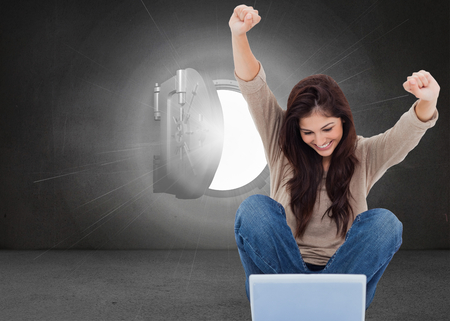 composite image: Composite image of pretty brunette cheering while using laptop Stock Photo