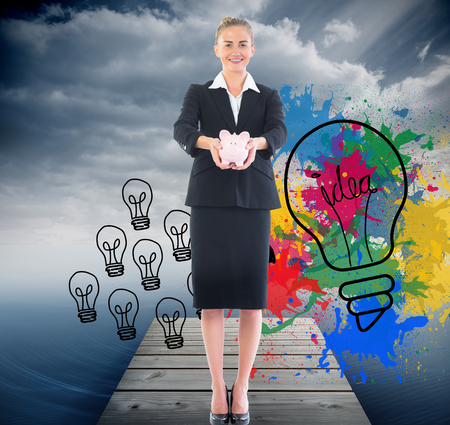 composite image: Composite image of happy blonde businesswoman holding a pink piggy bank Stock Photo