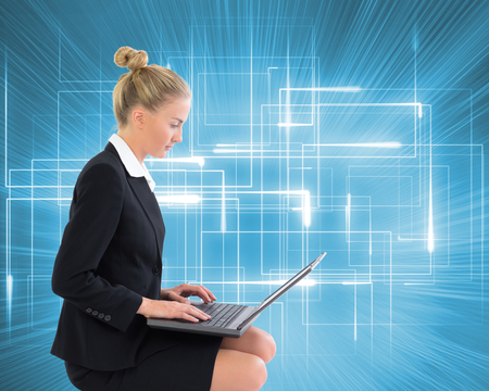 proportionate: Composite image of blonde businesswoman using laptop
