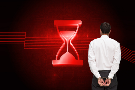 restraining: Composite image of rear view of young businessman wearing handcuffs on white background Stock Photo