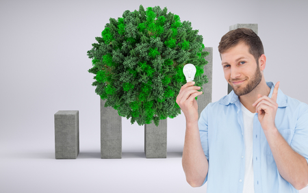 Composite image of charming model holding a bulb in right hand photo