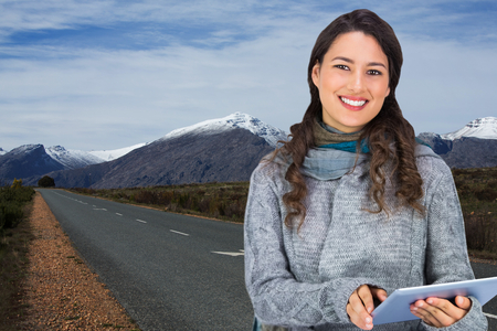 Composite image of smiling model wearing winter clothes holding her tablet photo