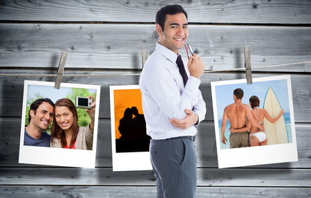 Composite image of smiling businessman holding glasses photo