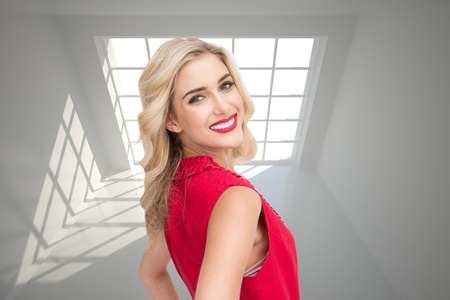 Composite image of smiling attractive blonde standing hands on hips photo