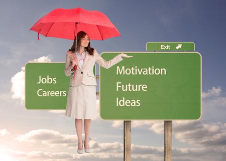 Composite image of attractive businesswoman holding red umbrella photo