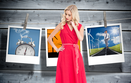 Composite image of elegant blonde standing hand on hip in red dress photo