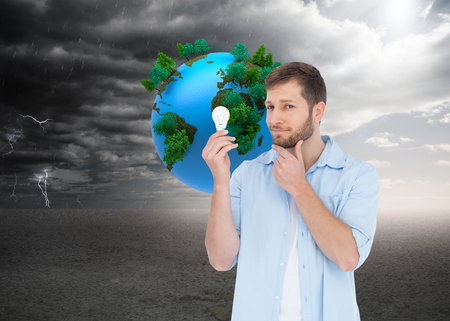 Composite image of handsome model holding a bulb  photo