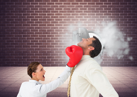 Composite image of businesswoman hitting a businessman with boxing gloves photo