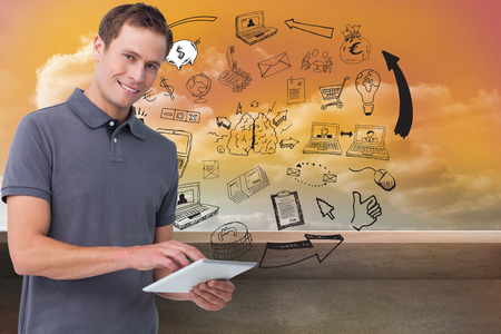 Composite image of smiling young man with tablet computer photo