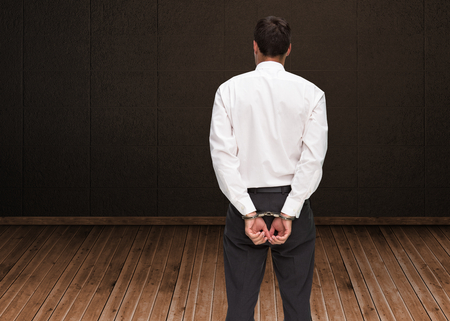 restraining device: Composite image of rear view of young businessman wearing handcuffs Stock Photo