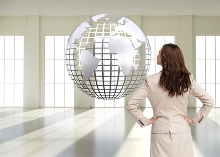 Composite image of businesswoman standing back to camera with hands on hips photo
