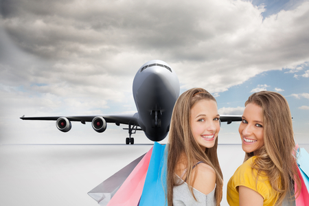 Composite image of two young women with shopping bags photo