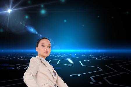 Composite image of unsmiling asian businesswoman pointing photo