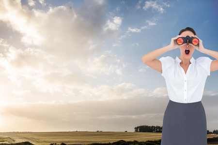 Composite image of shocked elegant businesswoman looking through binoculars while posing photo