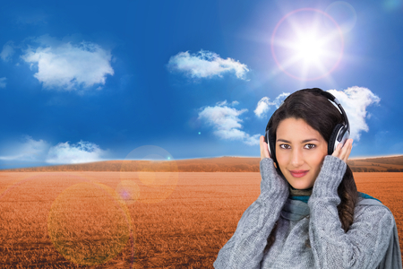 Composite image of beautiful model wearing winter clothes listening to music photo