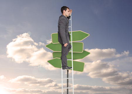 Composite image of stern businessman standing on ladder peering photo