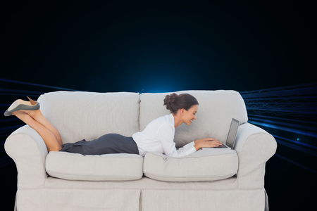 Composite image of smiling business woman lying on couch using laptop photo