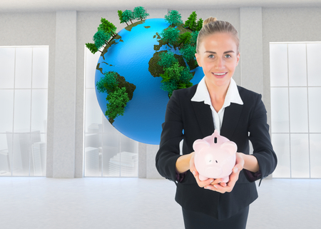 Composite image of blonde businesswoman holding pink piggy bank photo