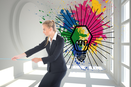 Composite image of blonde businesswoman pulling a rope photo