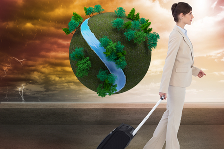 Composite image of serious businesswoman pulling suitcase photo