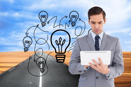 jumbled: Composite image of businessman holding a tablet computer