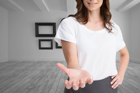 Composite image of attractive happy brunette presenting her hand photo