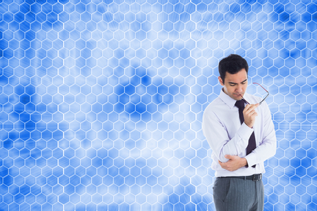 Composite image of thinking businessman holding glasses photo