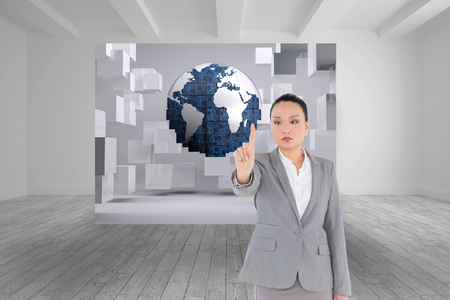 unsmiling: Composite image of unsmiling asian businesswoman pointing Stock Photo