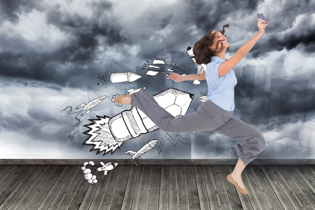Composite image of happy classy businesswoman jumping while holding smartphone photo