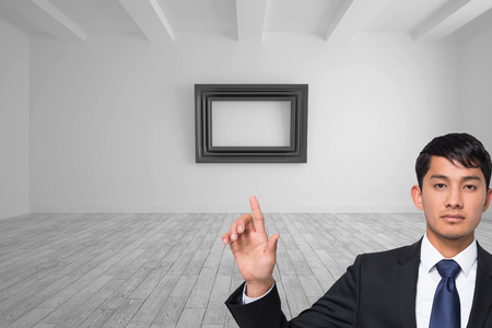 Composite image of unsmiling businessman touching photo