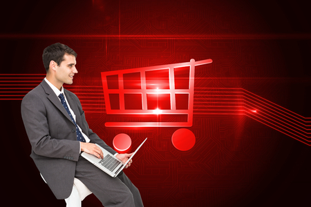 Composite image of businessman using laptop sitting on chair photo