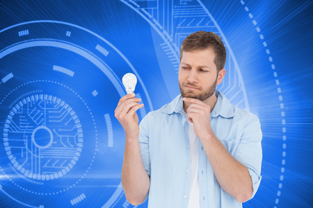 sceptical: Composite image of sceptical model holding a bulb  Stock Photo
