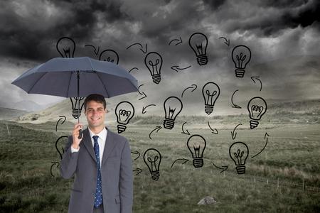 Composite image of happy businessman holding grey umbrella photo
