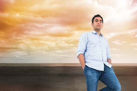 Composite image of unsmiling casual man standing photo