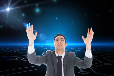 Composite image of unsmiling businessman with arms raised photo