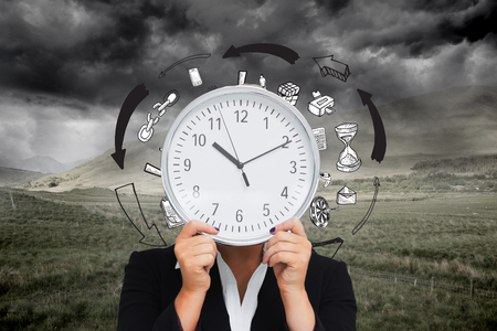 Composite image of businesswoman in suit holding a clock photo