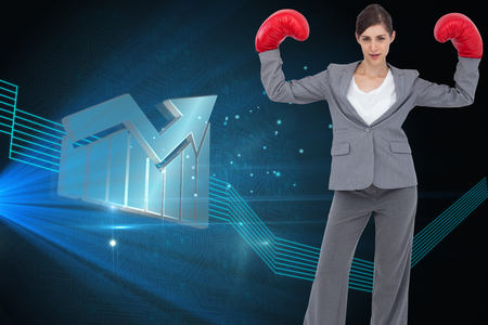 Composite image of businesswoman with boxing gloves photo