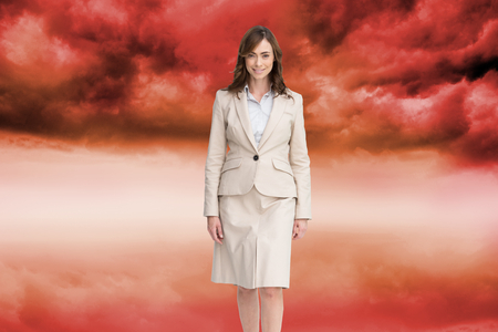 Composite image of smiling brunette businesswoman walking photo