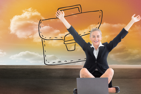 Composite image of attractive blonde businesswoman sitting in front of laptop with arms up photo