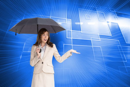 Composite image of elegant businesswoman holding black umbrella photo
