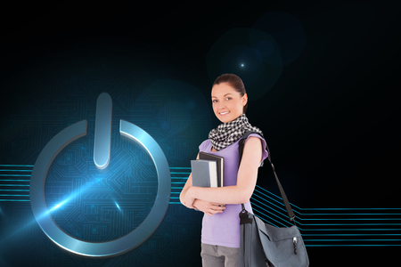 Composite image of attractive student holding books and her bag while standing photo
