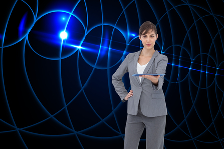 Composite image of attractive businesswoman holding tablet pc photo