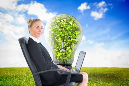 Composite image of blonde businesswoman sitting on swivel chair with laptop photo