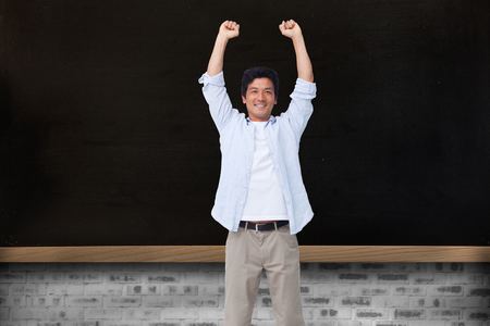 Composite image of cheering male with arms up photo