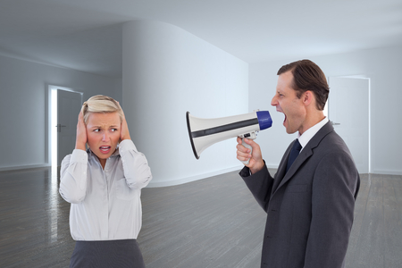 Composite image of businessman shouting at colleague with his bullhorn Imagens